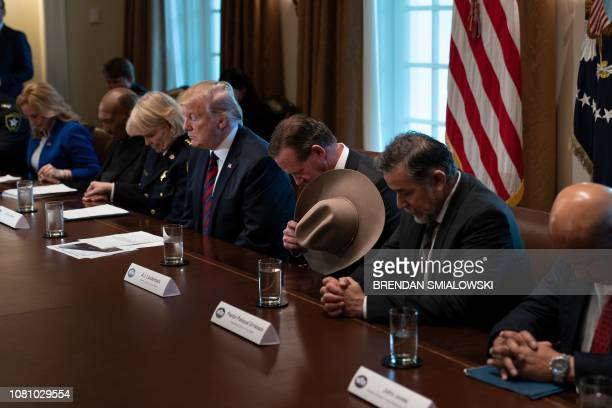 US President Donald Trump and others listen to a prayer during a meeting on border security in the Cabinet Room of the White House January 11 2019 in...
