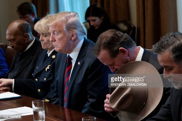 US President Donald Trump and others listen to a prayer during a meeting about border security in the Cabinet Room of the White House January 11 2019...