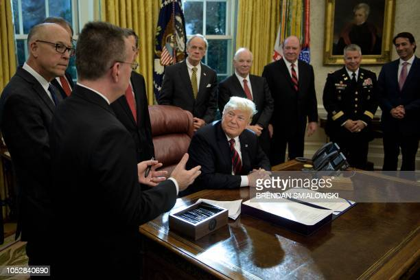 US President Donald Trump and others listen while pastor Andrew Brunson speaks during a bill signing for S3021 in the Oval Office of the White House...