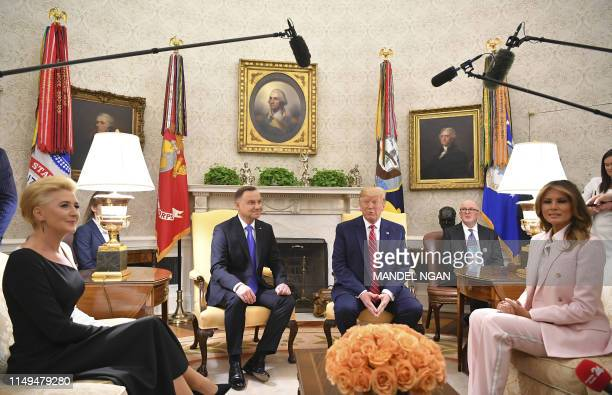 US President Donald Trump and Poland's President Andrzej Duda take part in an Oval Office meeting flanked by their wives US First Lady Melania Trump...