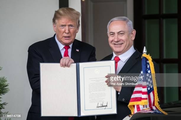President Donald Trump and Prime Minister of Israel Benjamin Netanyahu show members of the media the proclamation Trump signed on recognizing...