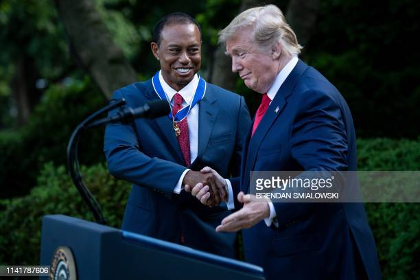 US President Donald Trump and professional golfer Tiger Woods shake hands during a Presidential Medal of Freedom ceremony in the Rose Garden of the...