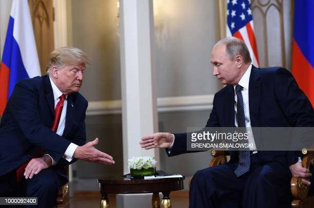 President Donald Trump and Russian President Vladimir Putin reach to shake hands before a meeting in Helsinki on July 16 2018