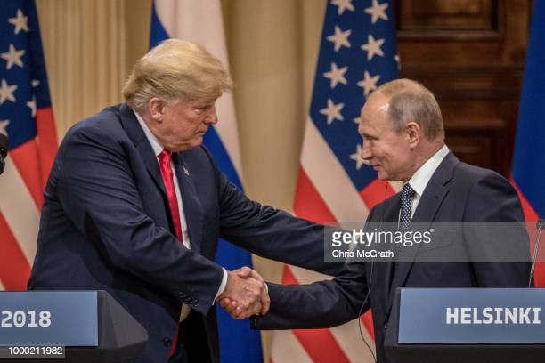 S President Donald Trump and Russian President Vladimir Putin shake hands during a joint press conference after their summit on July 16 2018 in...
