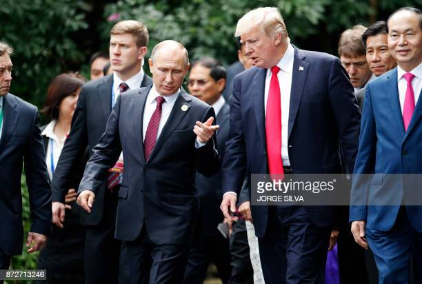 US President Donald Trump and Russia's President Vladimir Putin chat as they walk together to take part in the 'family photo' during the AsiaPacific...