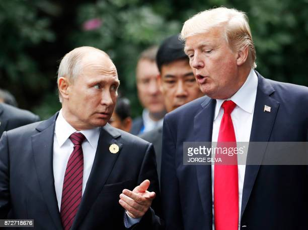 US President Donald Trump and Russia's President Vladimir Putin talk as they make their way to take the family photo during the AsiaPacific Economic...