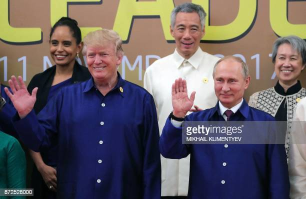 US President Donald Trump and Russia's President Vladimir Putin wave as they pose for a group photo ahead of the AsiaPacific Economic Cooperation...