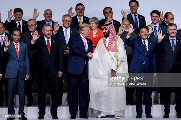 President Donald Trump and Saudi Arabia's Crown Prince Mohammed bin Salman shake hands during a group photo of members during the G20 Summit at the...