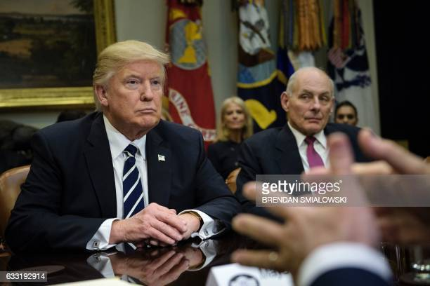 US President Donald Trump and Secretary of Homeland Security John Kelly listen while Rudy Giuliani speaks a meeting on cyber security in the...