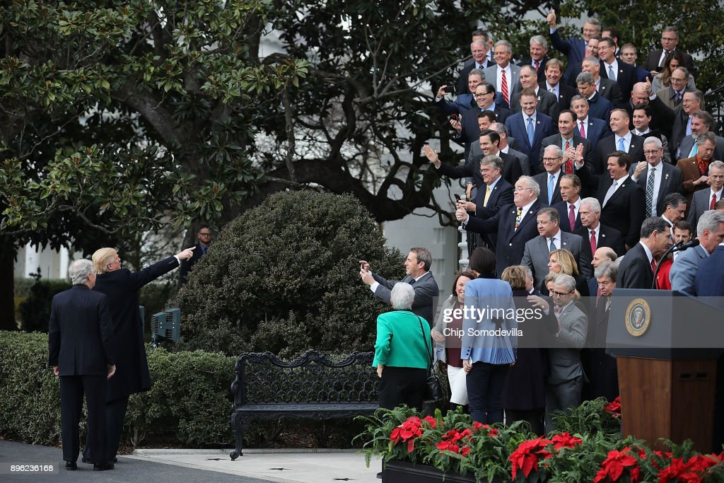 U.S. President Donald Trump (2nd L) and Senate Majority Leader Mitch McConnell (R-KY) acknowledge Republican members of the House and Senate at the consclustion of an event celebrating the Tax Cuts and Jobs Act on the South Lawn of the White House December 20, 2017 in Washington, DC. The tax bill is the first major legislative victory for the GOP-controlled Congress and Trump since he took office almost one year ago.