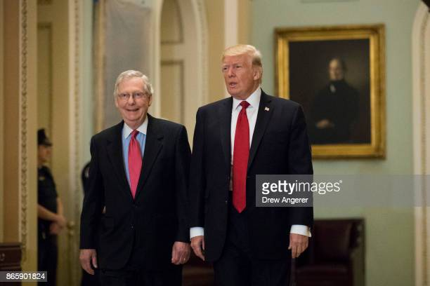 S President Donald Trump and Senate Majority Leader Mitch McConnell walk to a lunch with Senate Republicans on Capitol Hill October 24 2017 in...