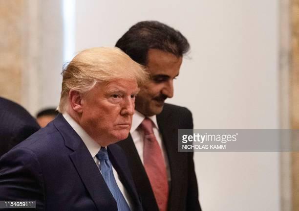 President Donald Trump and Sheikh Tamim bin Hamad al-Thani, Emir of Quatar, take their seats at a dinner at the Treasury Department in Washington,...