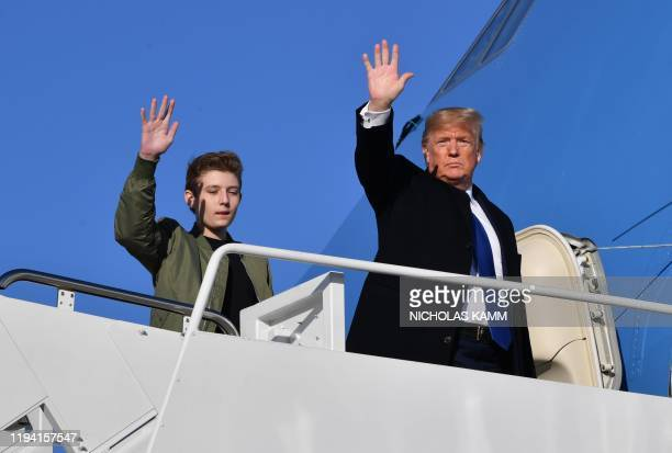 US President Donald Trump and son Barron Trump wave while making their way to board Air Force One at Andrews Airforce Base Maryland on January 17...