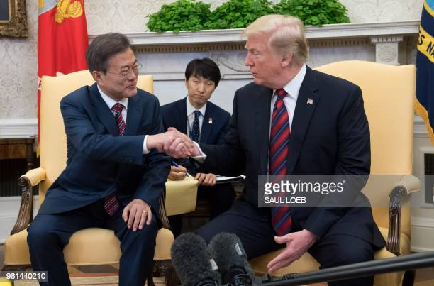 President Donald Trump and South Korean President Moon Jae-in shake hands during a meeting in the Oval Office of the White House in Washington, DC,...