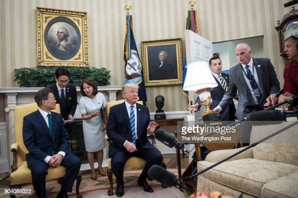 President Donald Trump and South Korean President Moon Jaein watch as Director of Oval Office Operations Keith Schiller right reacts to a lamp being...