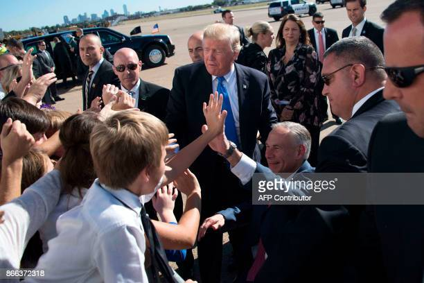 US President Donald Trump and Texas Governor Greg Abbott greet students as they arrive at Dallas Love Field in Dallas Texas on October 25 2017 / AFP...