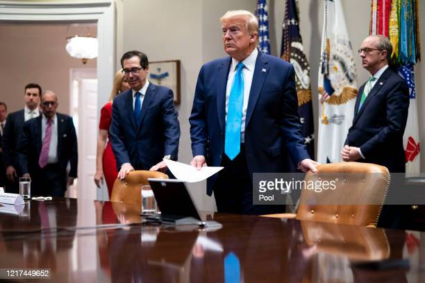 S President Donald Trump and Treasury Secretary Steven Mnuchin arrive for a video conference with representatives of large banks and credit card...