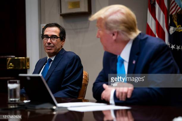 President Donald Trump and Treasury Secretary Steven Mnuchin participate in a video conference with representatives of large banks and credit card...