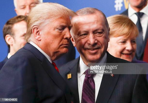 President Donald Trump and Turkey's President Recep Tayyip Erdogan leave the stage after the family photo to head to the plenary session at the NATO...