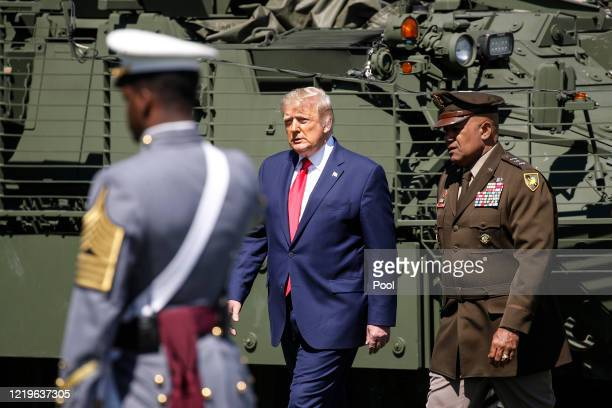 President Donald Trump and United States Military Academy superintendent Darryl A. Williams walk to the stand in front of graduating cadets during...
