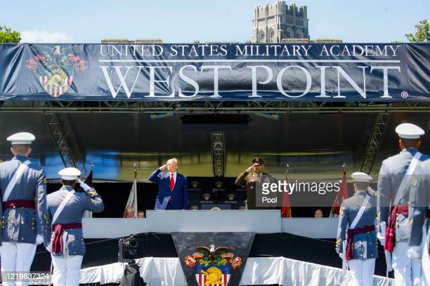 President Donald Trump and United States Military Academy superintendent Darryl A. Williams salute graduating cadets during commencement ceremonies...
