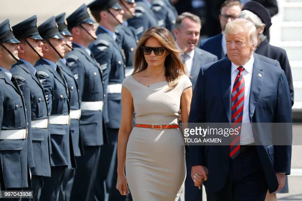 US President Donald Trump and US First Lady Melania Trump are greeted by an honour guard of Royal Air Force presonnel after disembarking Air Force...