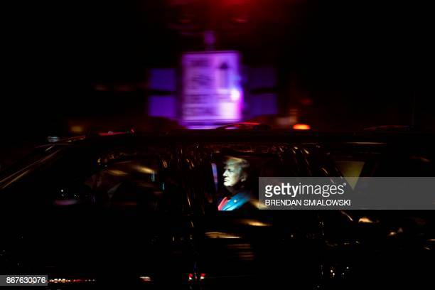 US President Donald Trump and US first lady Melania Trump are seen in an armored vehicle as they travel from the Trump International Hotel to the...