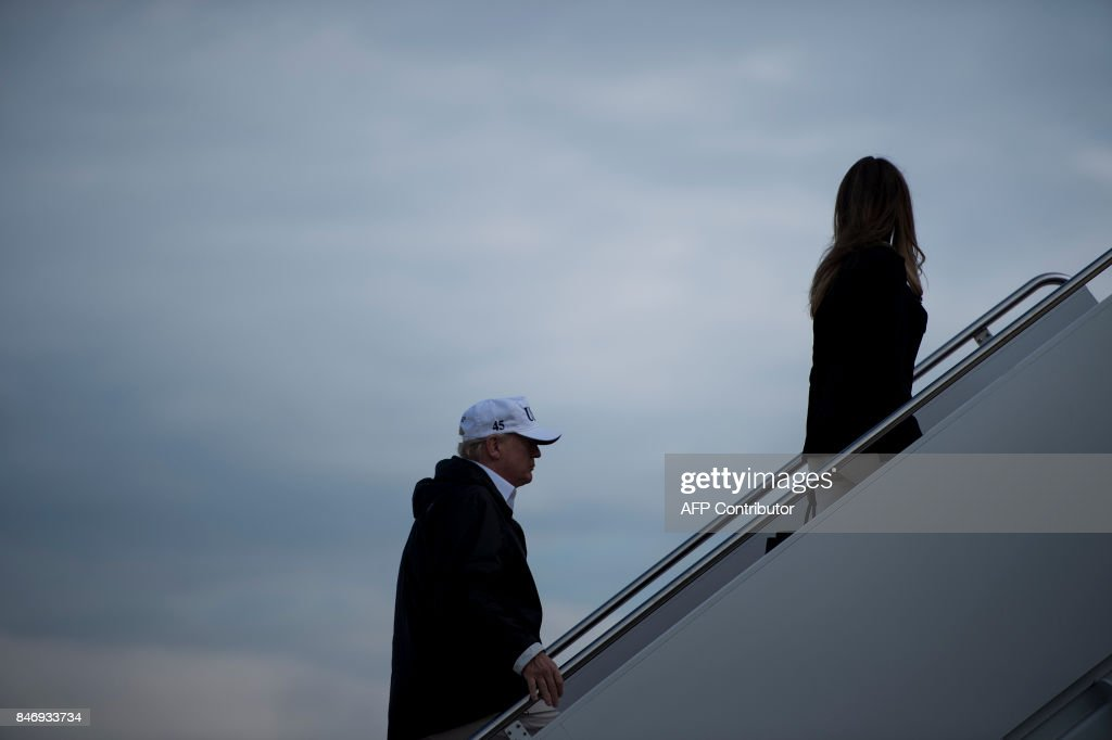 US President Donald Trump and US First Lady Melania Trump board Air Force One at Andrews Air Force Base in Maryland on September 14, 2017, as they travel to Florida . The Trumps will visit areas affected by Hurricane Irma. / AFP PHOTO / Brendan Smialowski