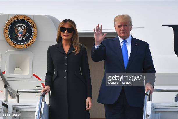 US President Donald Trump and US First Lady Melania Trump disembark from Air Force One after landing at the CaenCarpiquet Airport in Carpiquet...