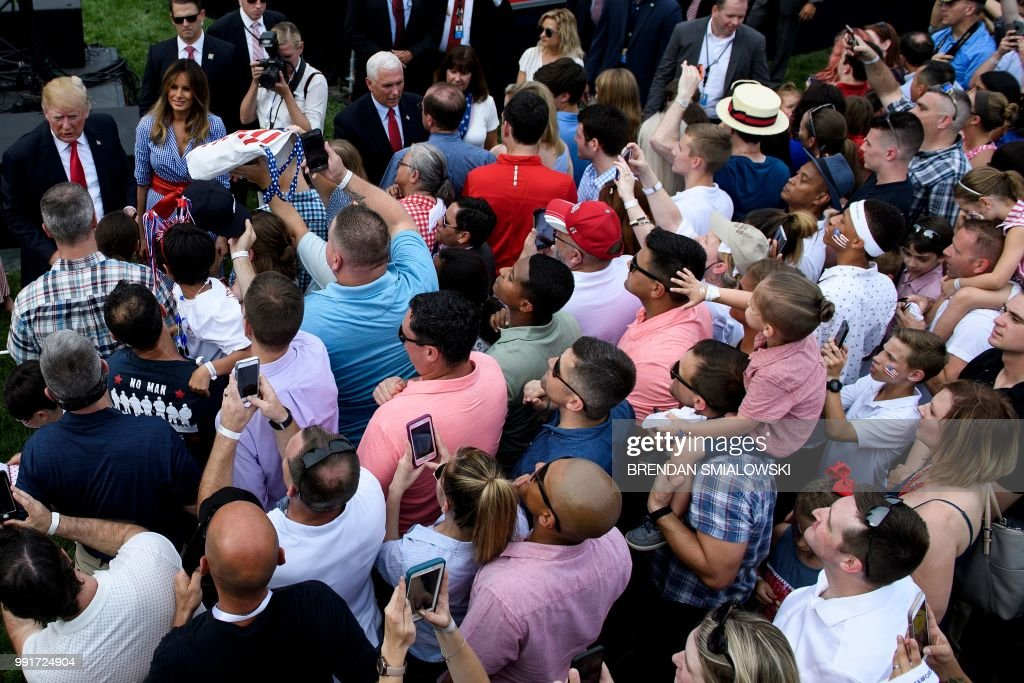 US President Donald Trump (L) and US First Lady Melania Trump greet guests during an Independence Day picnic for military families on the South Lawn of the White House July 4, 2018 in Washington, DC.