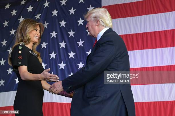 US President Donald Trump and US First Lady Melania Trump hug each other on stage during a meeting with US military personnel and families at Naval...