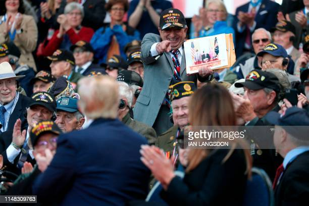 US President Donald Trump and US First Lady Melania Trump look at a supporter greeting them during the FrenchUS ceremony at the Normandy American...