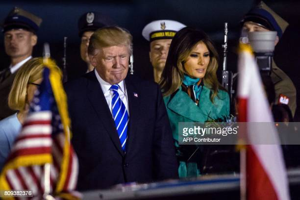 US President Donald Trump and US First Lady Melania Trump react after stepping off Air Force One upon their arrival at Chopin Airport in Warsawon...