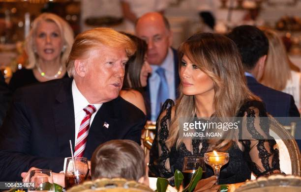 US President Donald Trump and US First Lady Melania Trump sit down for Thanksgiving dinner at his MaraLago resort in Palm Beach Florida on November...