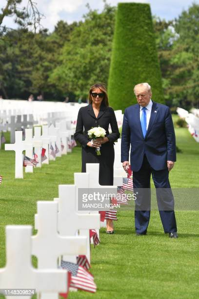 US President Donald Trump and US First Lady Melania Trump visit graves after a FrenchUS ceremony at the Normandy American Cemetery and Memorial in...