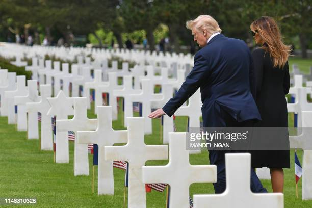 President Donald Trump and US First Lady Melania Trump visit graves after a French-US ceremony at the Normandy American Cemetery and Memorial in...