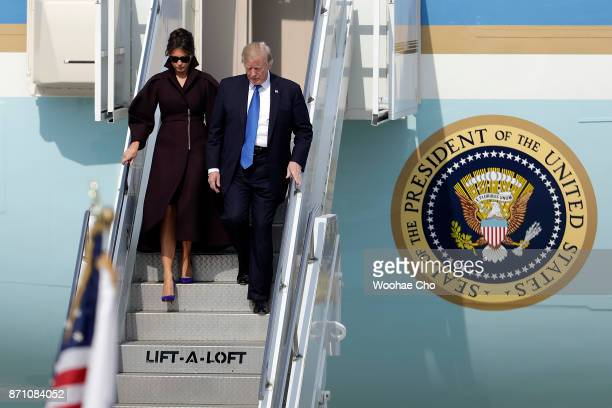 S President Donald Trump and US First Lady Melania Trump walk down a flight of stairs after stepping out of Air Force One as they arrive at Osan Air...