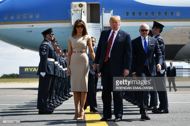 US President Donald Trump and US First Lady Melania Trump walk on the tarmac after disembarking Air Force One at Stansted Airport north of London on...