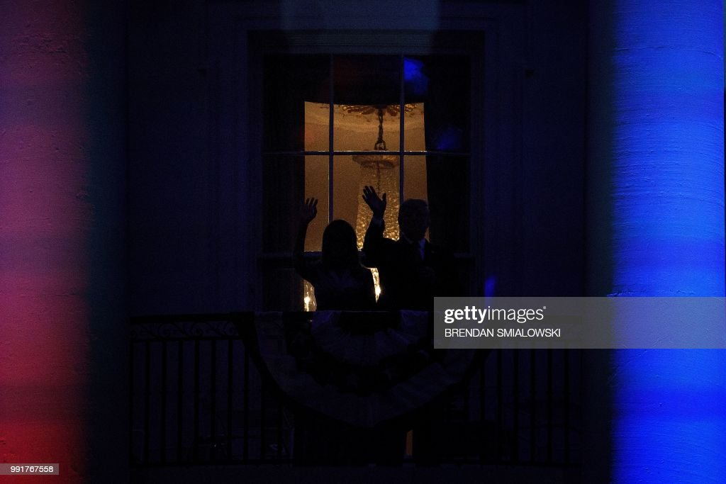 US President Donald Trump and US first lady Melania Trump wave after watching fireworks from the Truman Balcony during a Independence Day celebration on the South Lawn of the White House July 4, 2018 in Washington, DC.