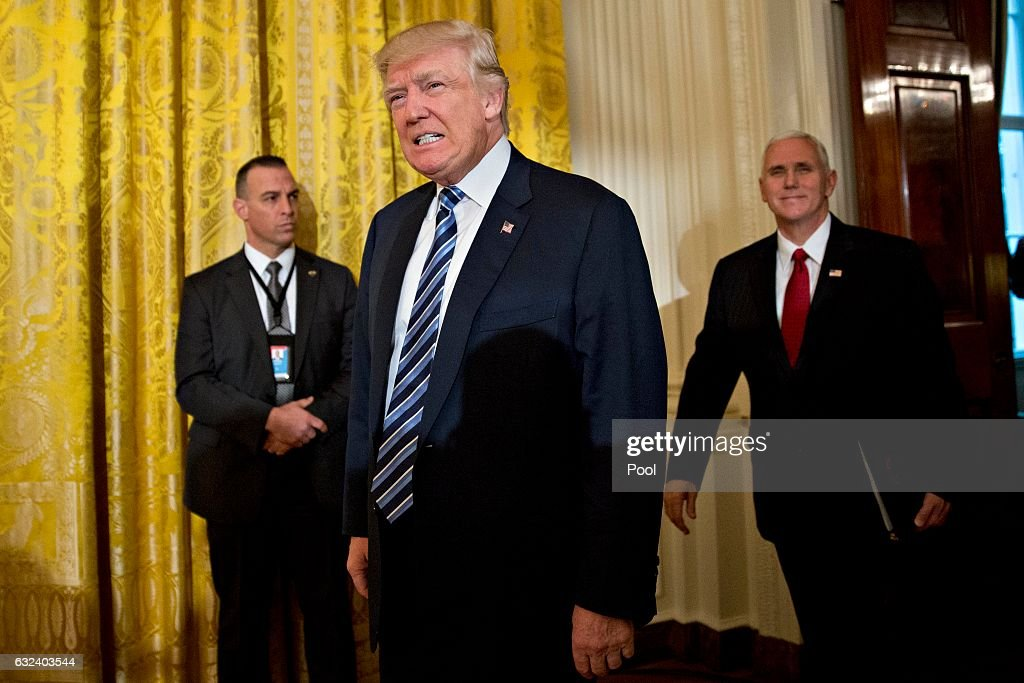 U.S. President Donald Trump and U.S. Vice President Mike Pence (R) arrive to a swearing in of White House senior staff in the East Room of the White House on January 22, 2017 in Washington, DC. Trump today mocked protesters who gathered for large demonstrations across the U.S. and the world on Saturday to signal discontent with his leadership, but later offered a more conciliatory tone, saying he recognized such marches as a 'hallmark of our democracy.'