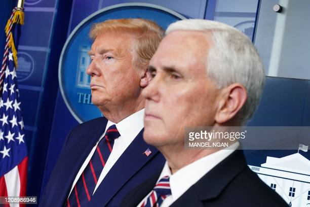 President Donald Trump and US Vice President Mike Pence look on during the daily briefing on the novel coronavirus, COVID-19, in the Brady Briefing...