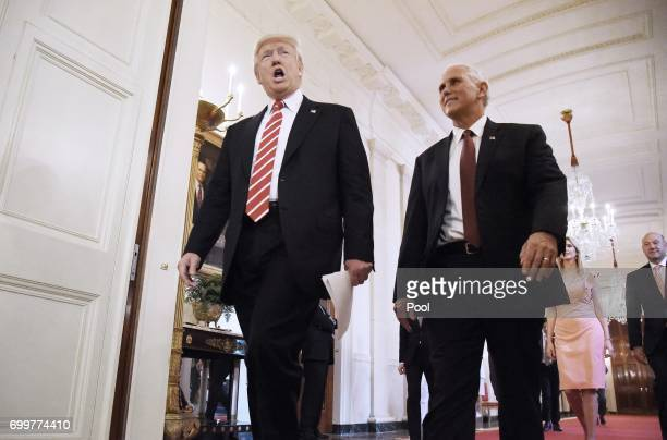 US President Donald Trump and VicePresident Mike Pence arrive in the East Room to participates in the American Leadership in Emerging Technology...