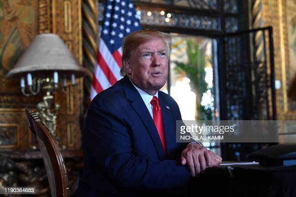 President Donald Trump answers questions from reporters after making a video call to the troops stationed worldwide at the Mar-a-Lago estate in Palm...