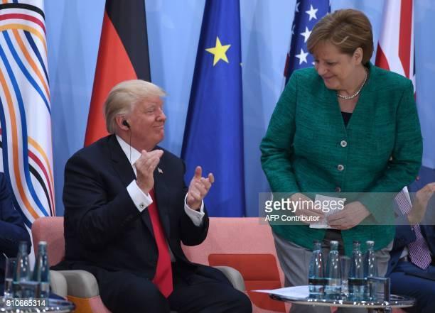 US President Donald Trump applauds after German Chancellor Angela Merkel gave a speech during the panel discussion 'Launch Event Women's Entrepreneur...