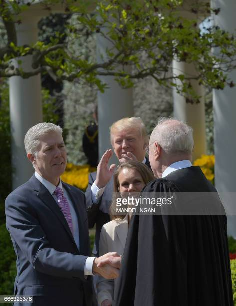 US President Donald Trump applauds after Justice Anthony Kennedy administered the oath of office to Neil Gorsuch as an associate justice of the US...