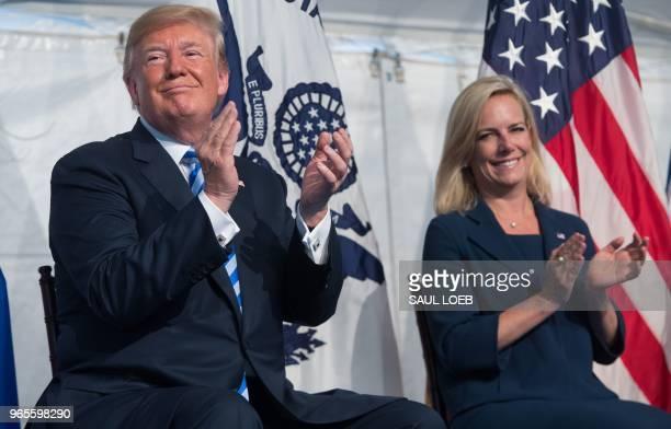 US President Donald Trump applauds alongside Secretary of Homeland Security Kirstjen Nielsen during a Change of Command ceremony as Admiral Karl...