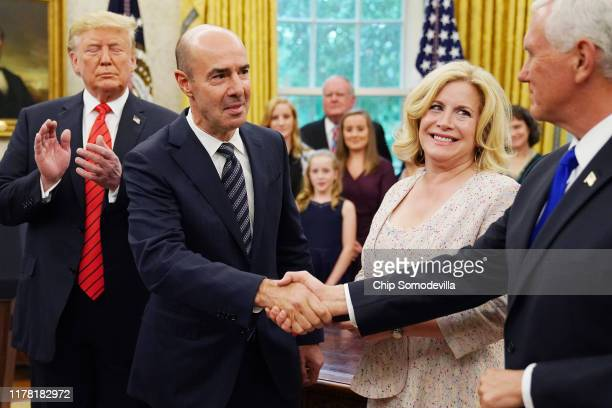 S President Donald Trump applauds as Labor Secretary Eugene Scalia is congratulated by Vice President Mike Pence as his wife Patricia Scalia looks on...