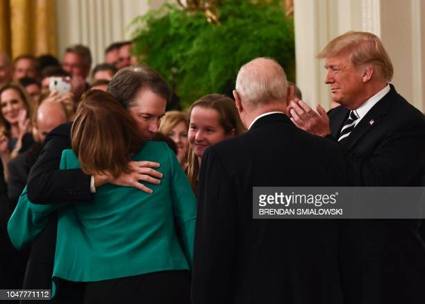 US president Donald Trump applauds as newly swornin Associate Justice of the US Supreme Court Brett Kavanaugh hugs his wife Ashley Estes October 8...
