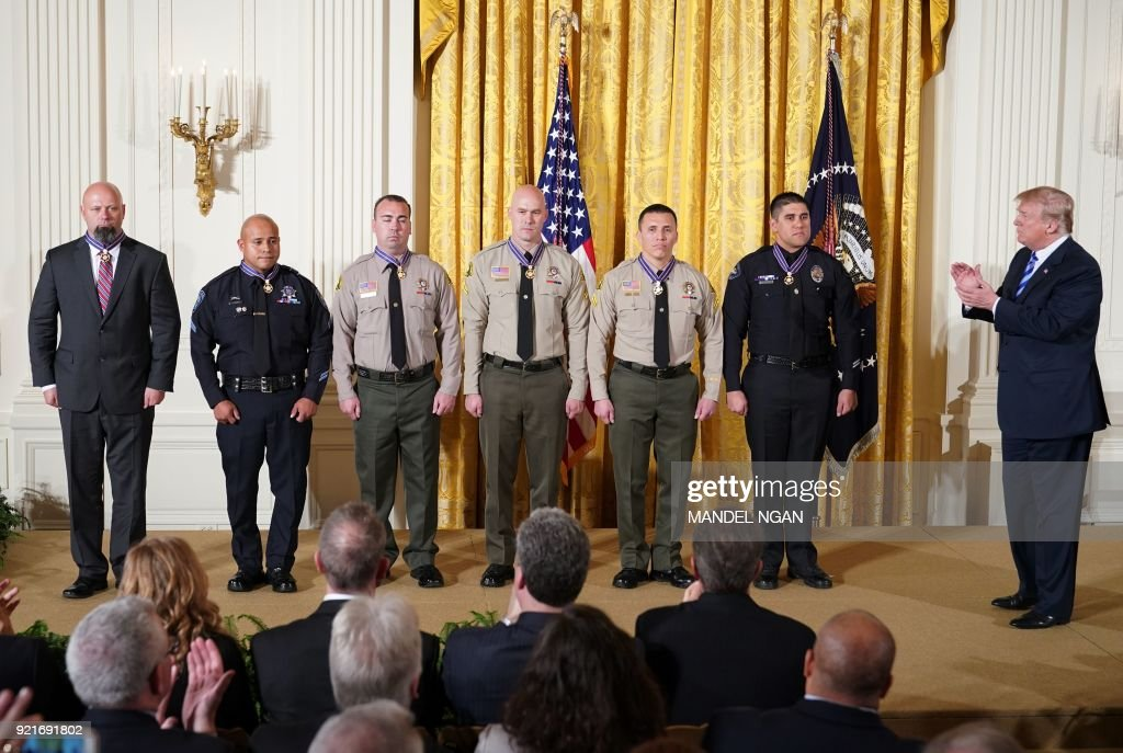 US President Donald Trump applauds (from left) District Attorney Investigator Chad Johnson, San Bernardino County District Attorneys Office, CA; Detective Brian Olvera, San Bernardino Police Department, CA; Deputy Shaun Wallen, San Bernardino County Sheriff's Department, CA; Detective Bruce Southworth, San Bernardino County Sheriff's Department, CA; Corporal Rafael Ixco, San Bernardino County Sheriff's Department, CA; Officer Nicholas Koahou, Redlands Police Department, CA; after presenting them with the Public Safety Medal of Valor Award during a ceremony in the East Room of the White House on February 20, 2018 in Washington, DC. /