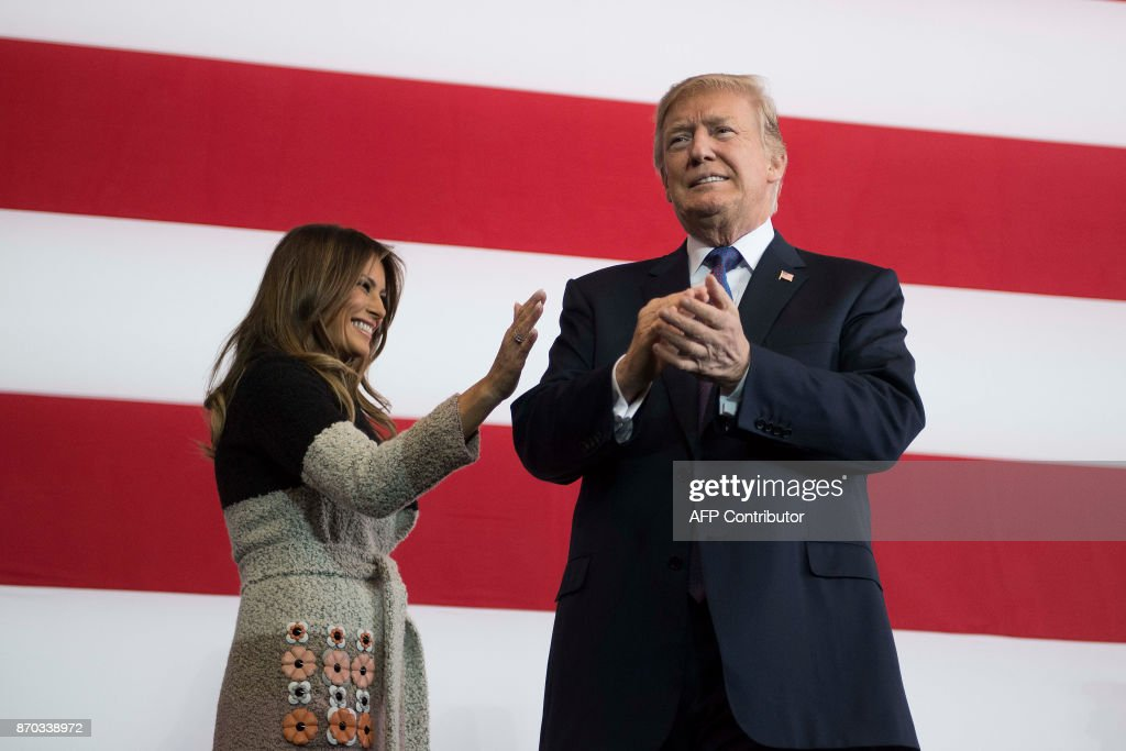President Donald Trump (R) applauds he arrives with his wife Melania Trump (L) to speak to US military personnel at Yokota Air Base at Fussa in Tokyo on November 5, 2017. Trump touched down in Japan on November 5, kicking off the first leg of a high-stakes Asia tour set to be dominated by soaring tensions with nuclear-armed North Korea. /